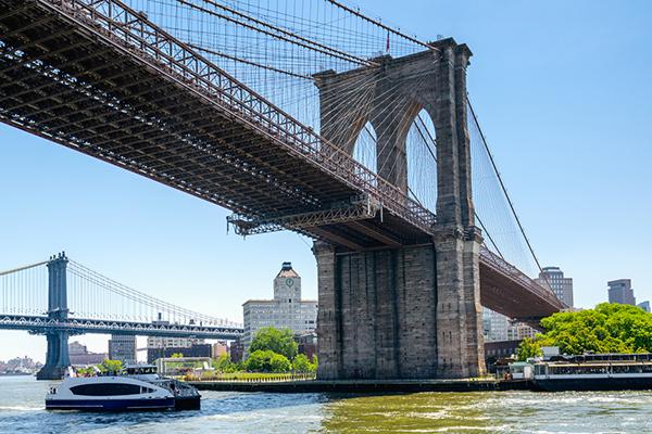 Under The Brooklyn Bridge, New York City. East River, Brooklyn Bridge and Manhattan Bridge. Boat Tour Journey